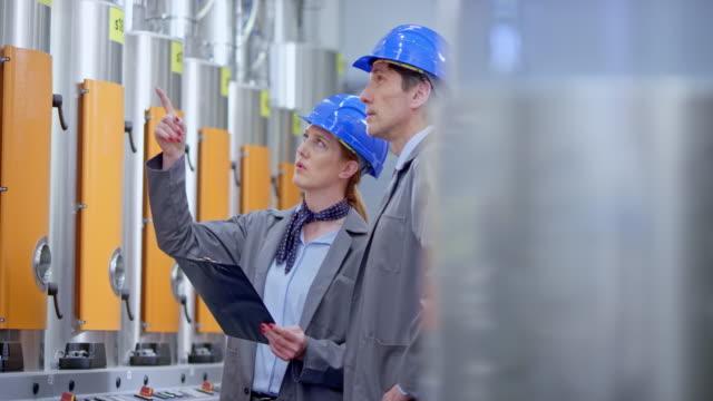 stockvideo's en b-roll-footage met ds kaukasische mannelijke en vrouwelijke ingenieur controleren van de waarden op de machines in de controlekamer - effectiviteit