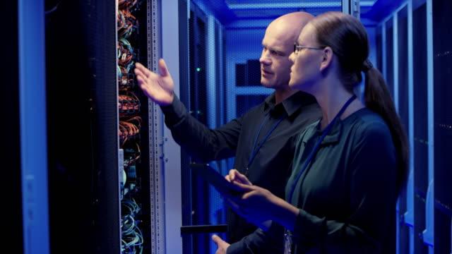 ds 白人男性と女性システム管理者サーバー接続ケーブルの確認 - 保護点の映像素材/bロール