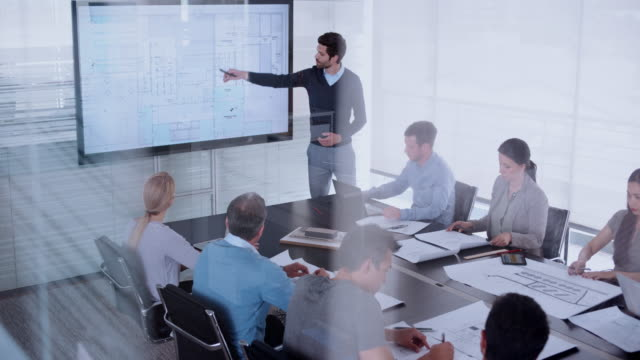 Caucasian male architect giving a presentation of the plans using a screen in conference room