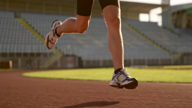 vidéos et rushes de athlète masculin de slo mo ds tu caucasienne en cours d'exécution dans le stade ensoleillé - piste de compétition