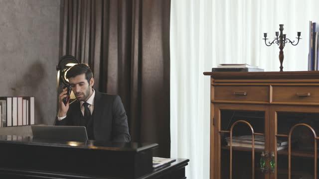 vídeos y material grabado en eventos de stock de caucasian male business man in classical style executive office, using mobile phone and laptop - vestimenta de negocios formal