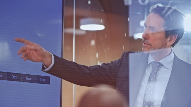 caucasian male businessman doing a presentation in the glass conference room - autorità video stock e b–roll
