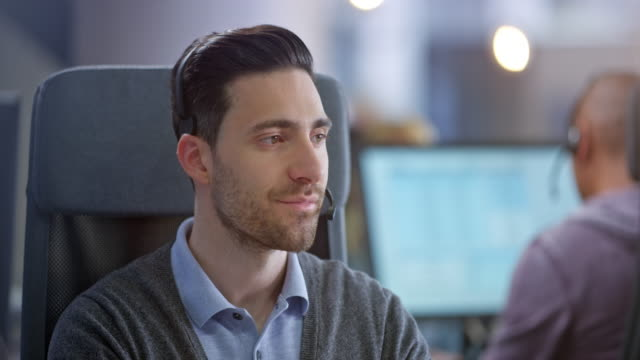caucasian male call center agent smiling while providing customer support - it support stock videos & royalty-free footage