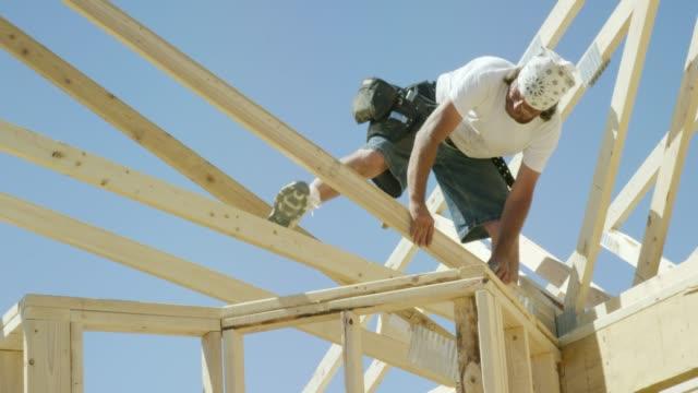 vídeos de stock, filmes e b-roll de um trabalhador masculino caucasiano da construção em seus forties anexa um fardo de madeira quadro do telhado a uma estrutura com um martelo e pregos ao moldar uma casa em um dia desobstruído, ensolarado - imperfeição