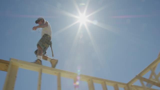 vídeos de stock, filmes e b-roll de um trabalhador masculino caucasiano da construção em seus forties equilibra ao andar através da parte superior de uma casa moldada em um dia desobstruído, ensolarado com um guindaste hidráulico no fundo - imperfeição