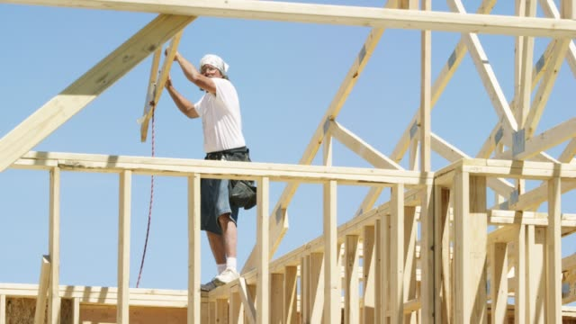 A Caucasian Male Construction Worker in His Forties Guides a Wooden Roof Truss into Place while Framing a House on a Clear, Sunny Day
