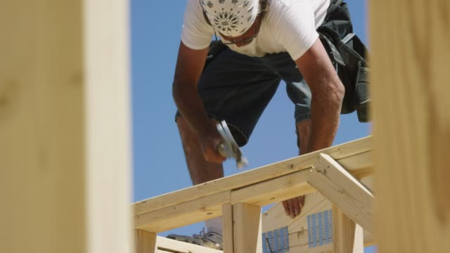 A Caucasian Male Construction Worker in His Forties Hammers While Framing a House on a Clear, Sunny Day