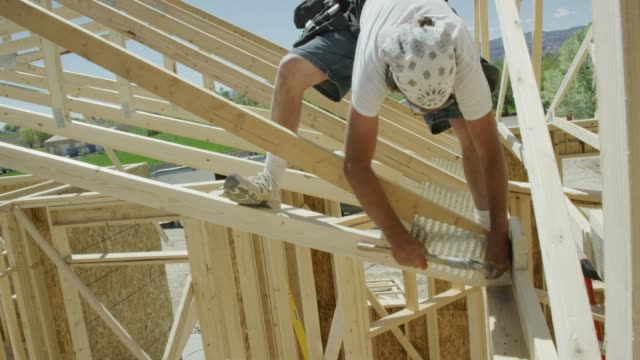 a caucasian male construction worker in his forties secures a framed wooden roof truss to a house using a hammer and nails before climbing to the center of the roof truss on a clear, sunny day - condition stock videos & royalty-free footage
