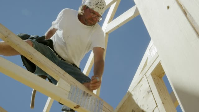 a caucasian male construction worker in his forties secures a framed wooden roof truss to a house using a hammer and nails on a clear, sunny day - hammer stock videos & royalty-free footage