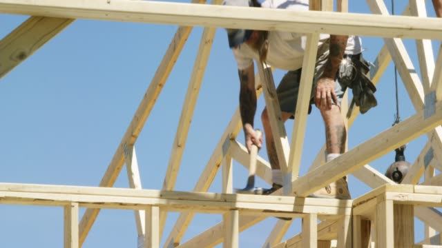 A Caucasian Male Construction Worker in His Forties Secures a Wooden Roof Truss to a Structure with a Hammer and Nails while Framing a House on a Clear, Sunny Day