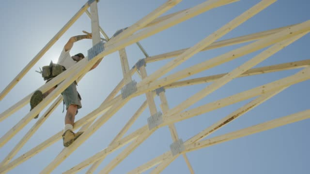 a caucasian male construction worker in his forties secures framed wooden roof trusses together with a ridge beam using a hammer and nails while framing a house on a clear, sunny day - roof beam stock videos & royalty-free footage