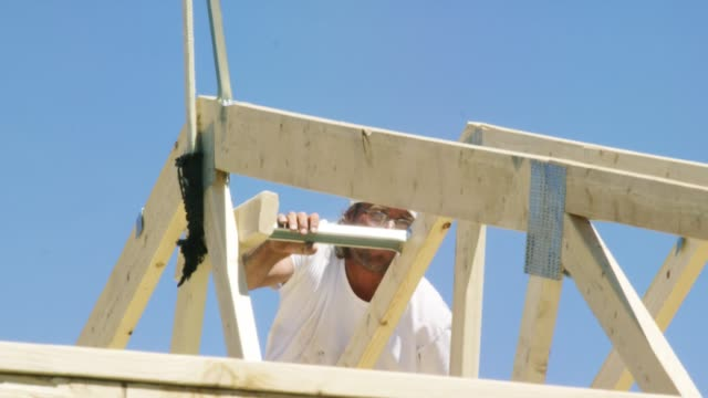 A Caucasian Male Construction Worker in His Forties Secures Ridge Supports to Wooden Roof Trusses with a Hammer and Nails while Framing a House on a Clear, Sunny Day