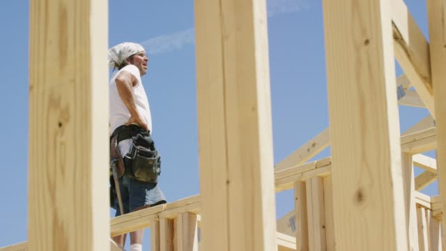 A Caucasian Male Construction Worker in His Forties Talks to Someone While Framing a House on a Clear, Sunny Day