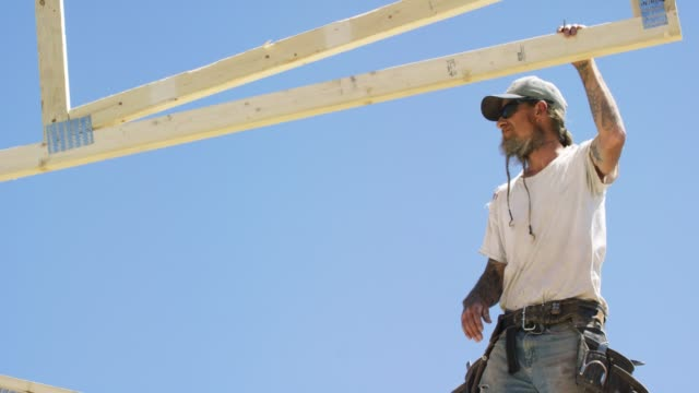 A Caucasian Male Construction Worker in His Forties with a Beard and Tattoos Guides a Wooden Roof Truss into Place on a Clear, Sunny Day