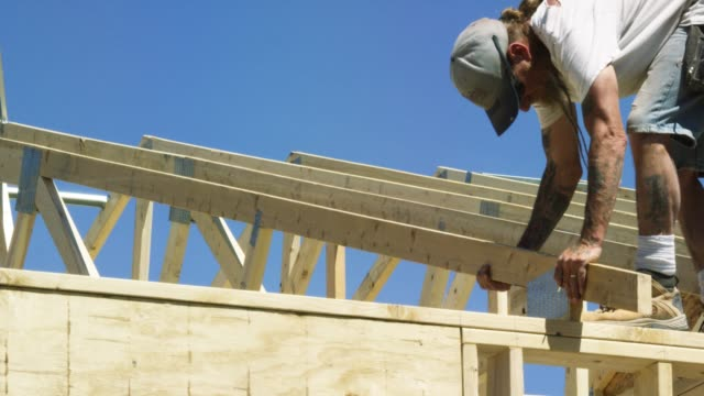 A Caucasian Male Construction Worker in His Forties with a Beard and Tattoos Guides a Wooden Roof Truss into Place and Secures it to a Structure with a Hammer and Nails while Framing a House on a Clear, Sunny Day