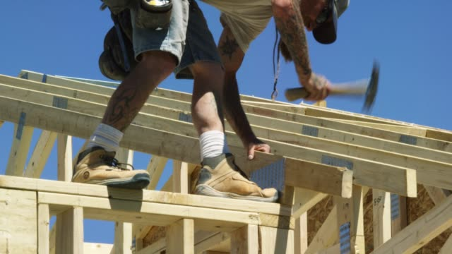 A Caucasian Male Construction Worker in His Forties with a Beard and Tattoos Secures a Wooden Roof Truss to a Structure with a Hammer and Nails while Framing a House on a Clear, Sunny Day