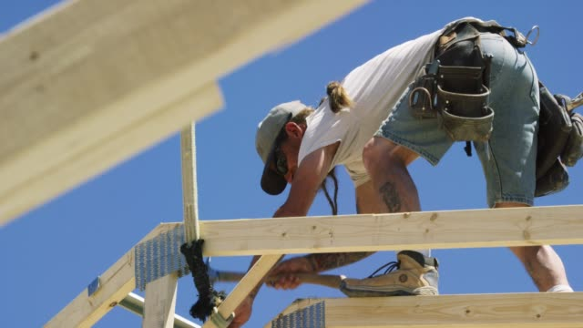 A Caucasian Male Construction Worker in His Forties with a Beard and Tattoos Hammers a Support Along a Roof Truss While Framing a House on a Clear, Sunny Day