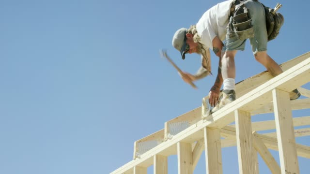 A Caucasian Male Construction Worker in His Forties with Tattoos Secures a Framed Wooden Roof Truss by Hammering a Nail to the Structure While Framing a House on a Clear, Sunny Day