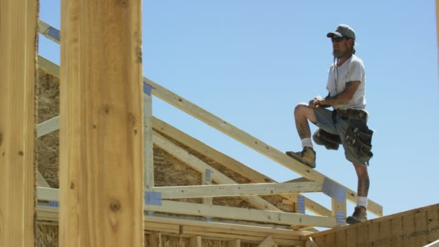 A Caucasian Male Construction Worker in His Forties with Tattoos Takes a Break While Standing with One Leg Up on the Top of a Framed House at a Construction Site on a Clear, Sunny Day