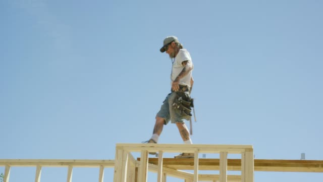 a caucasian male construction worker in his forties with tattoos balances while walking across the top of a framed house on a clear, sunny day - timber stock videos & royalty-free footage