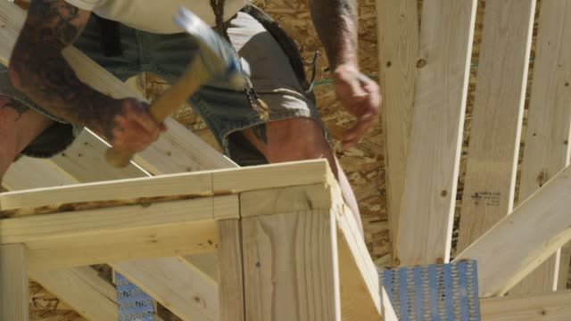 A Caucasian Male Construction Worker in His Forties with Tattoos Hammers While Framing a House on a Clear, Sunny Day