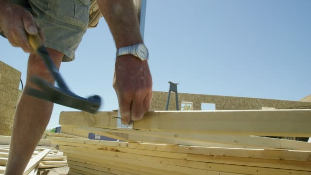 a caucasian male construction worker nails a metal beam into place with a hammer while framing at a construction site on a clear, sunny day - construction frame stock videos & royalty-free footage