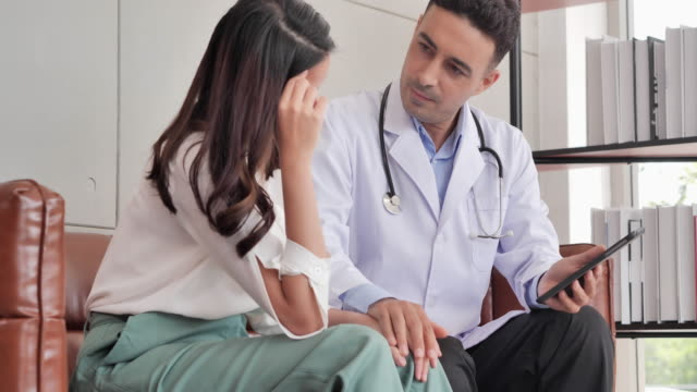 caucasian male doctor in consultation to her asian young women patient while holding hand to her patient help express empathy encourage tell diagnosis at medical visit at hospital.male medical staff - emotional support stock videos & royalty-free footage