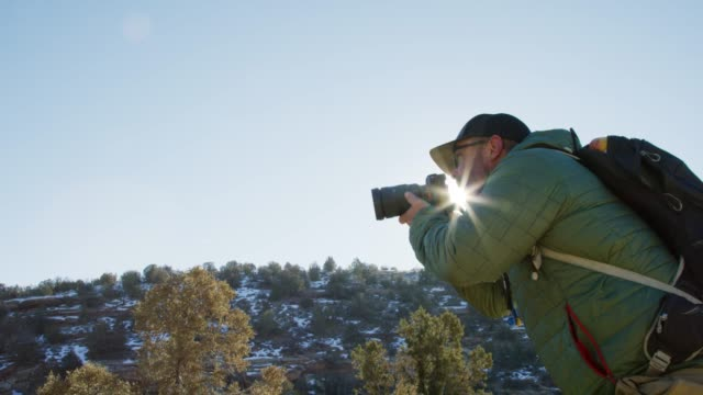 vídeos de stock e filmes b-roll de a caucasian male photographer in his forties dressed in hiking gear takes photographs in the high desert of western colorado in winter (near the colorado national monument - grand junction, colorado) - visor digital