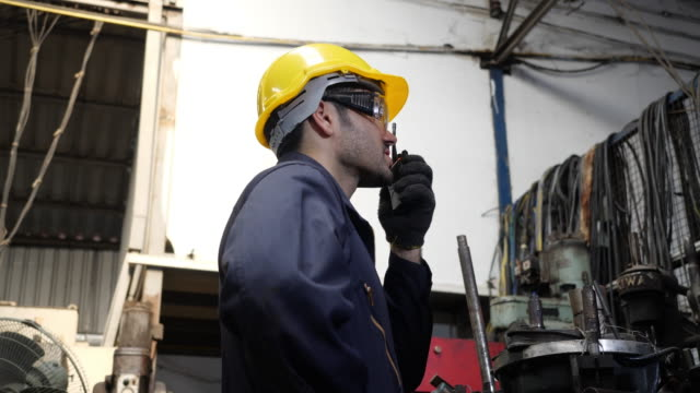 caucasian male professional engineer wearing hard hat talking using walkie talkie controls work in a factory. - form of communication stock videos & royalty-free footage