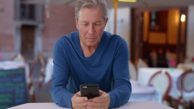caucasian male senior uses smartphone while sitting at restaurant in europe - mobilità video stock e b–roll