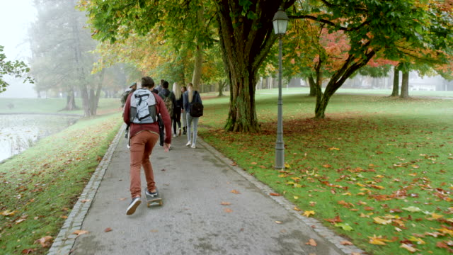 Caucasian male student riding his skateboard past a group of student walking through a park on a fall morning