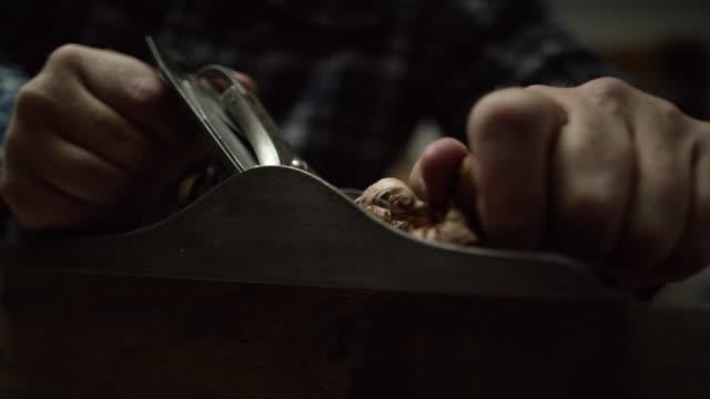 vídeos y material grabado en eventos de stock de un carpintero hombre caucásico en una camisa a cuadros utiliza un plano de mano vintage no.5 en el borde de una tabla de roble rojo crear virutas de madera - carpintero