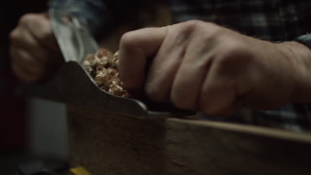 a caucasian male woodworker in a plaid shirt uses a no.5 vintage hand plane along the edge of a red oak board creating wood shavings - craftsperson stock videos & royalty-free footage
