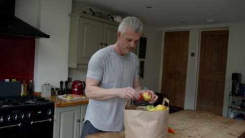 caucasian man at home unpacking his groceries - paper bag stock videos & royalty-free footage