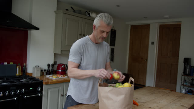 caucasian man at home unpacking his groceries - unpacking stock videos & royalty-free footage