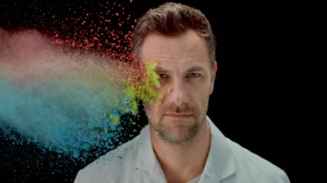 SLO MO Caucasian man being thrown multi colored powder dust into the face from the side