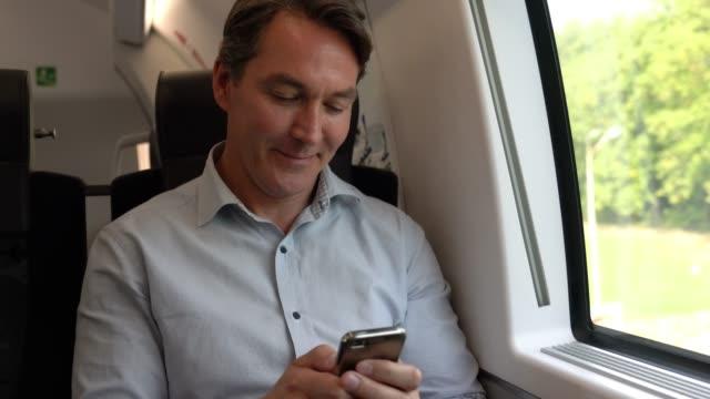 Kaukasische man woon-werkverkeer op de trein sms'en op zijn smartphone op zoek naar erg blij