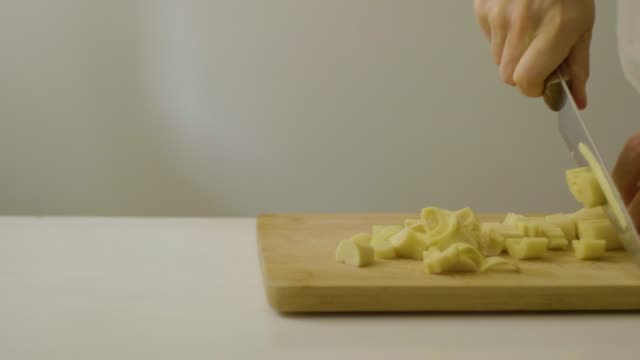 vídeos de stock, filmes e b-roll de caucasian man cutting palm hearts on a cutting board at a white table - comida e bebida