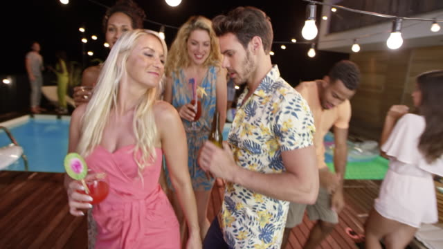 Caucasian man dancing with a female friend at a party by the pool at night