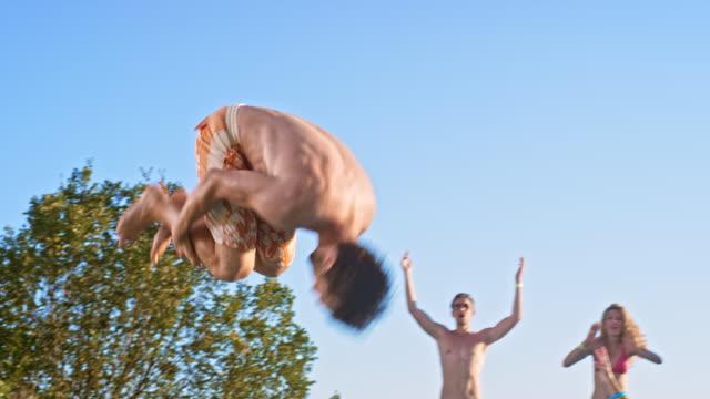 SLO MO DS blanke man doen een salto in het water op een pool party terwijl gestimuleerd door zijn vrienden