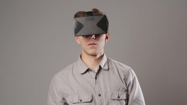 kaukasischer mann erlebt virtuelle realität durch ein vr-headset isoliert auf grauem hintergrund - schutzbrille freisteller stock-videos und b-roll-filmmaterial