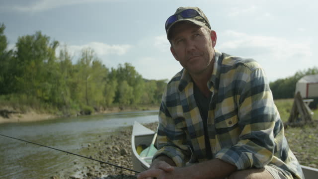 caucasian man fishing in boat - cap stock videos and b-roll footage