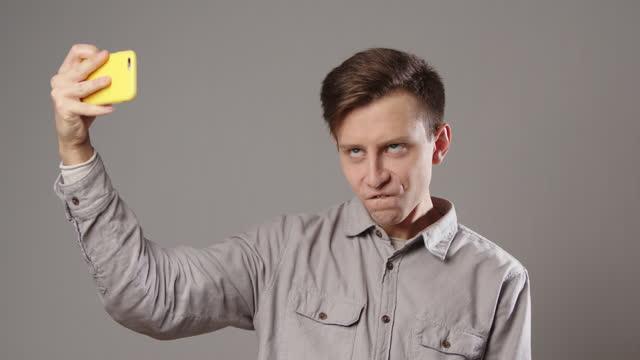 kaukasisk man rynkar pannan tar selfie på mobiltelefon på grå bakgrund - rynka ihop ansiktet bildbanksvideor och videomaterial från bakom kulisserna
