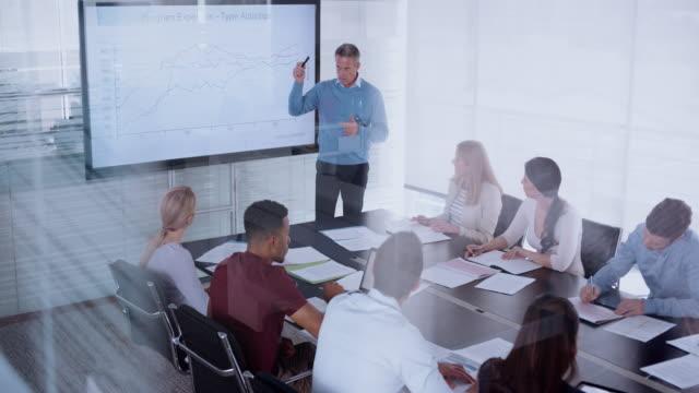 kaukasischen mann hält einen vortrag über den finanziellen aspekt des programms an seine kollegen im konferenzraum - stift stock-videos und b-roll-filmmaterial