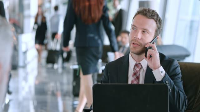 vidéos et rushes de homme de race blanche ds ayant une entreprise appelez dans le business lounge à l'aéroport - 25 29 ans
