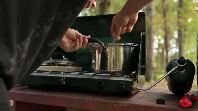 プロパンキャンプストーブで食べ物の料理をかき混ぜる30代の白人男性 - キャンプ用ストーブ点の映像素材/bロール