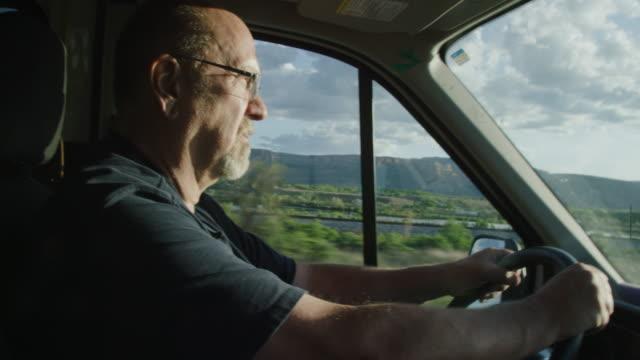 50代の白人男性が夜明け/日没時に西コロラド州の晴れた日にトラックを運転 - トラック運転手点の映像素材/bロール