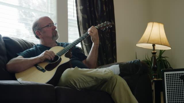 ein kaukasischer mann in seinen 50er jahren spielt eine akustische gitarre in einem wohnzimmer - gitarre stock-videos und b-roll-filmmaterial