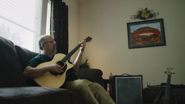 vídeos de stock, filmes e b-roll de um homem caucasiano em seus fifties joga uma guitarra acústica em uma sala de visitas - dedilhando instrumento
