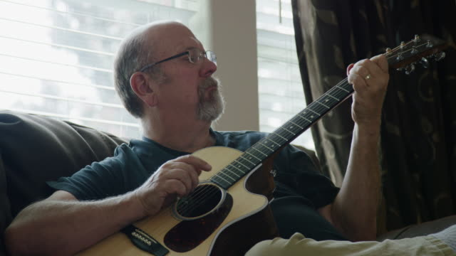 a caucasian man in his fifties plays an acoustic guitar in a living room - guitarist stock videos & royalty-free footage